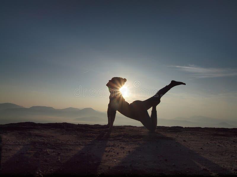 La jeune femme exécutent le yoga sur la falaise dans le matin photographie stock libre de droits
