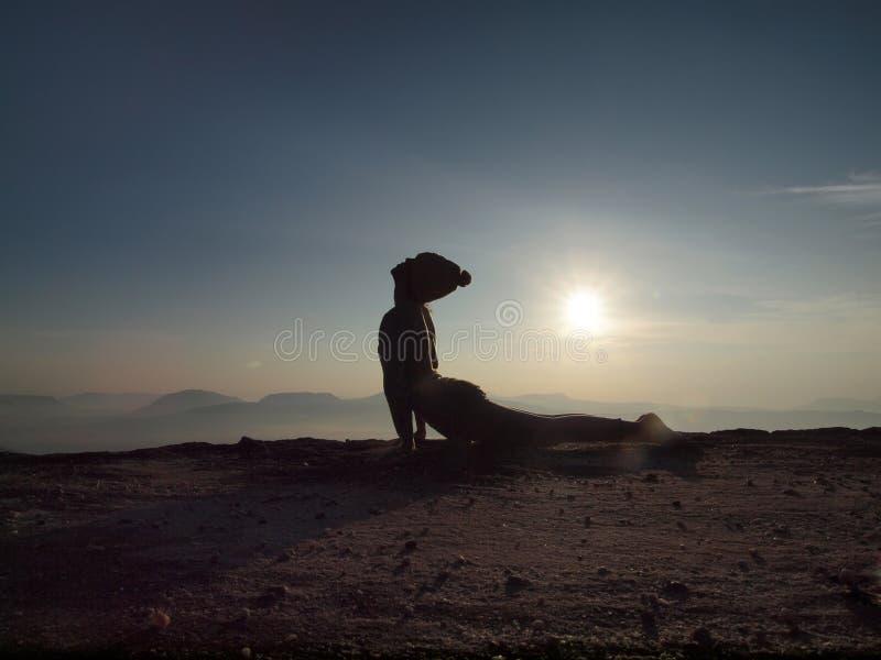 La jeune femme exécutent le yoga sur la falaise dans le matin photos stock