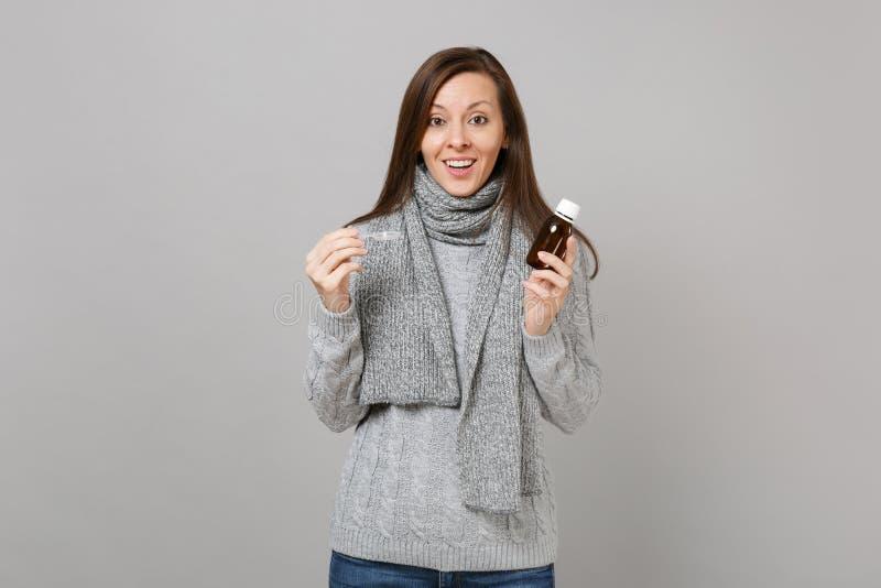 La jeune femme excitée dans le chandail gris, participation d'écharpe versent la médecine liquide dans la cuillère d'isolement su photos libres de droits