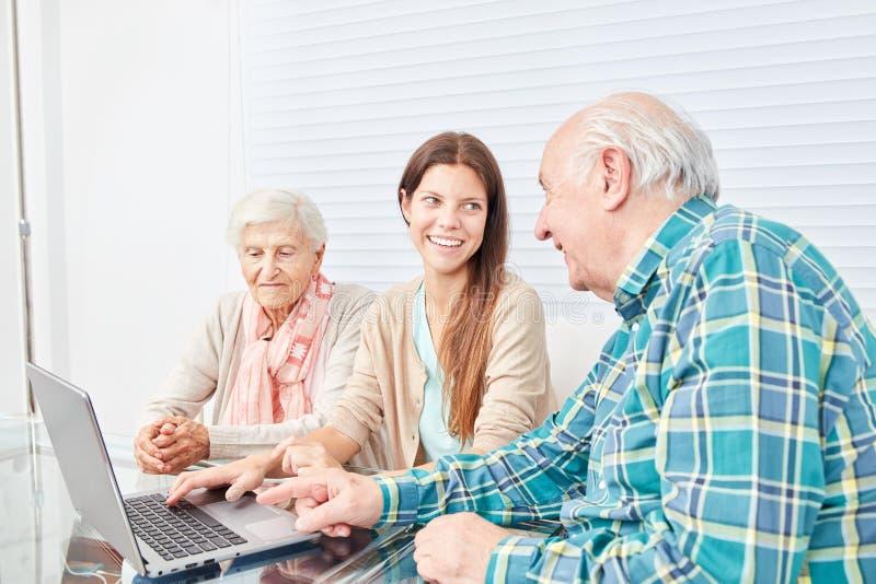 La jeune femme explique des couples d'aînés l'Internet photos stock