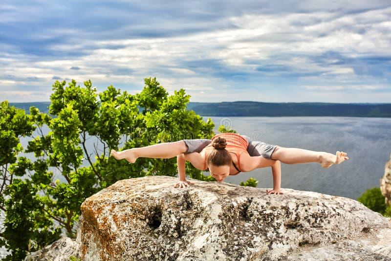 La jeune femme faisant la forme physique de yoga exerce extérieur dans le paysage de rivière photographie stock