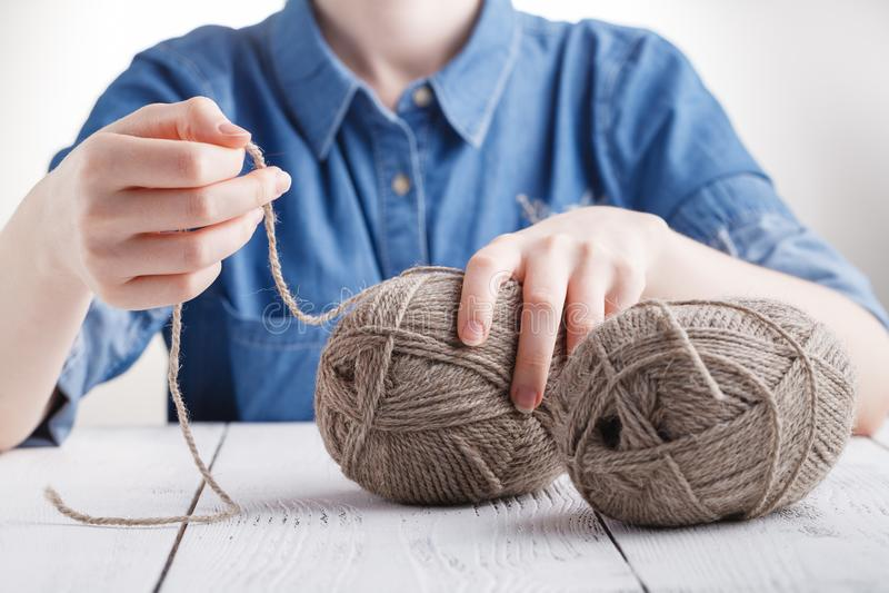 La jeune femme fait du crochet une couverture chaude avec la laine beige images libres de droits