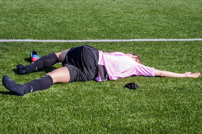 La jeune femme fait l'étirage après un match de football image stock