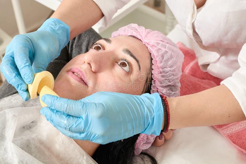 La jeune femme fait le massage facial professionnel dans le salon de beaut image stock