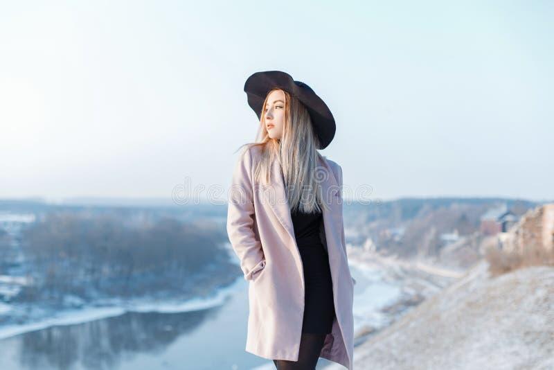 La jeune femme fascinante dans un manteau rose à la mode dans un chapeau élégant dans une robe tricotée noire se tient sur une mo photographie stock libre de droits
