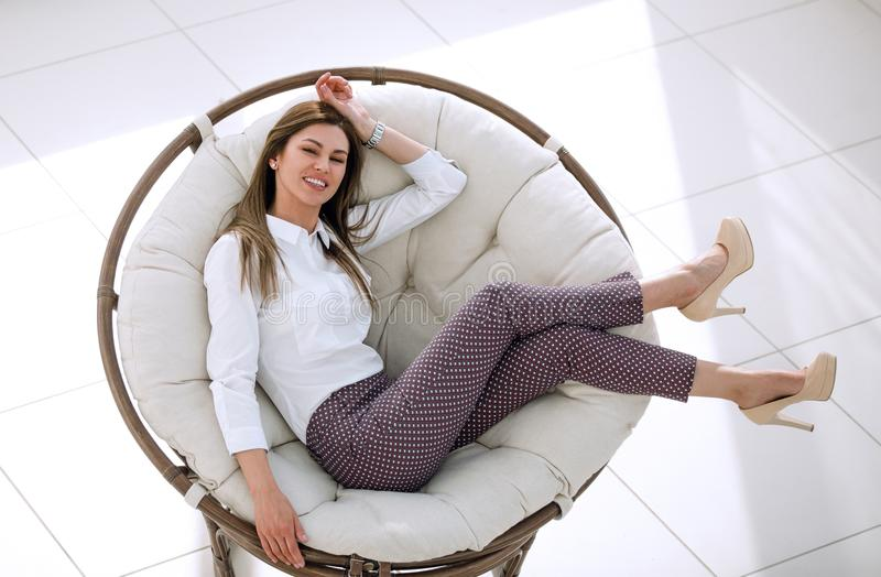 La jeune femme fatiguée détend dans une chaise ronde molle photographie stock libre de droits