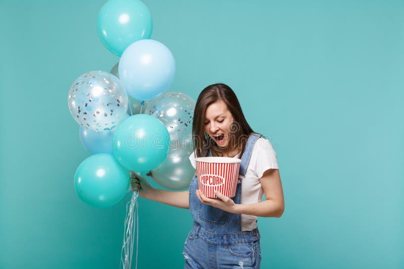 La jeune femme folle maintenant la bouche grande ouverte, tenant le seau de maïs éclaté et célébrant avec les ballons à air color photos stock