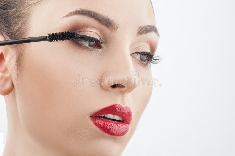 La jeune femme gaie applique le cosmétique photo stock