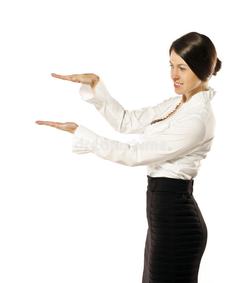 La jeune femme gaie dans le studio montre quelque chose image stock