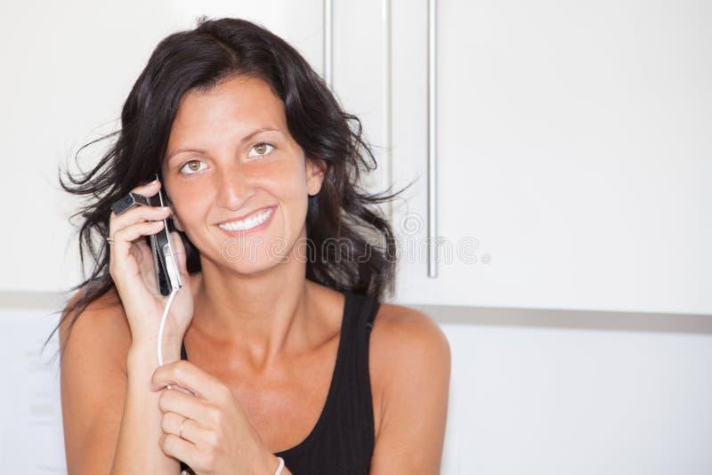 La jeune femme gaie de brune parlent à la maison au téléphone portable, fille bronzage de beauté dans la maison photo libre de droits
