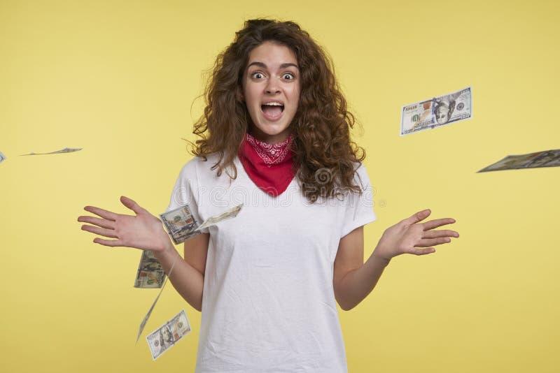 La jeune femme gaie gagne beaucoup d'argent liquide, au-dessus d'argent liquide volant et de fond jaune image libre de droits
