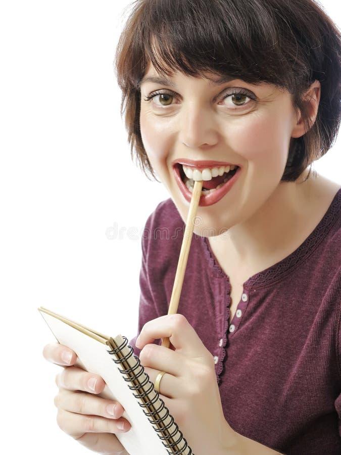 La jeune femme heureuse écrit quelque chose au cahier de travail images libres de droits