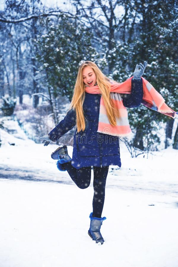 La jeune femme heureuse apprécient la neige en parc de ville d'hiver extérieur photos libres de droits