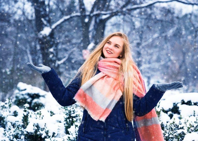 La jeune femme heureuse apprécient la neige en parc de ville d'hiver extérieur photographie stock libre de droits