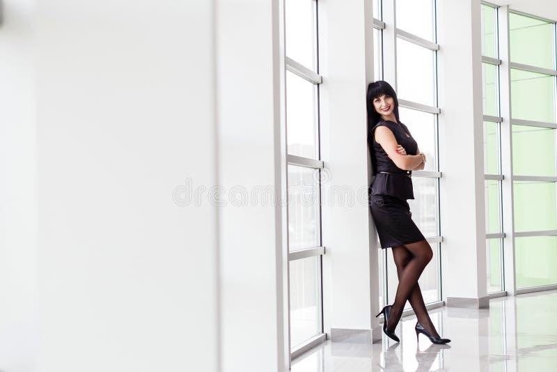 La jeune femme heureuse attirante de brune habillée dans un costume noir avec une jupe courte se tient près de la fenêtre dans le photo libre de droits