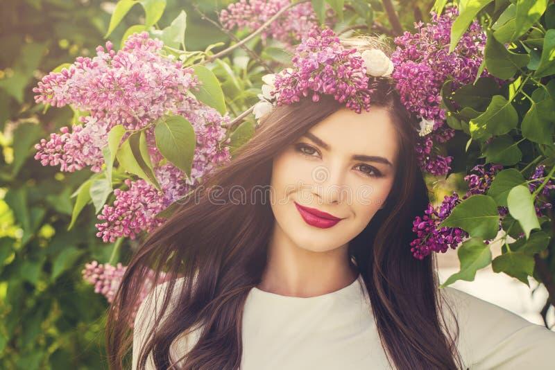 La jeune femme heureuse avec le ressort fleurit dehors images libres de droits