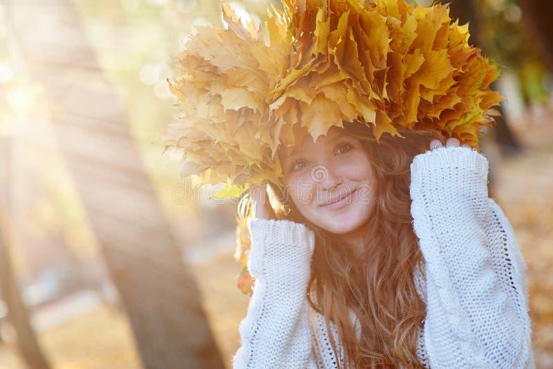 La jeune femme heureuse avec une guirlande de jaune laisse la marche dans le parc images stock