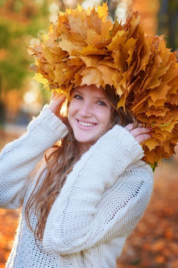 La jeune femme heureuse avec une guirlande de jaune laisse la marche dans le parc photographie stock libre de droits