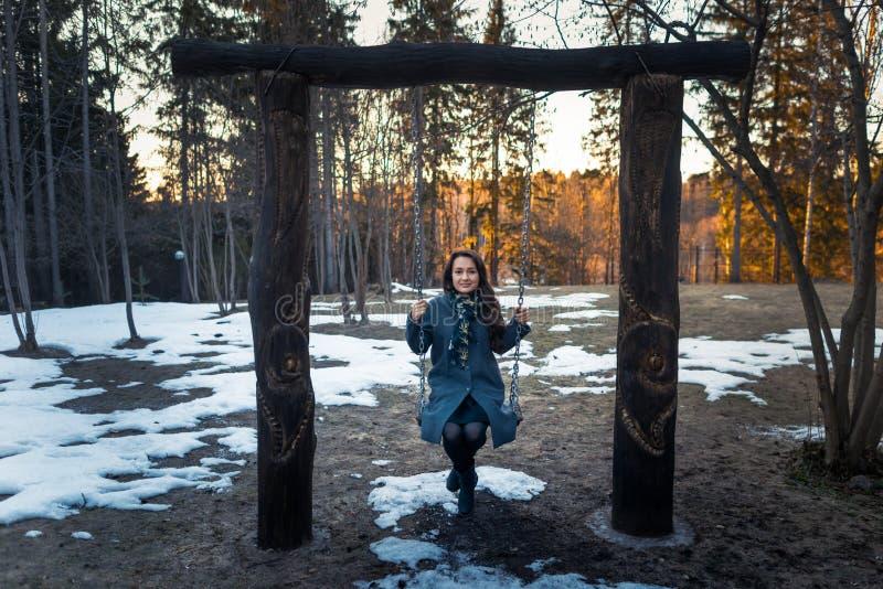 La jeune femme heureuse balançant sur une oscillation ont l'amusement et le sourire dans le parc dans le jour d'hiver ensoleillé  image libre de droits