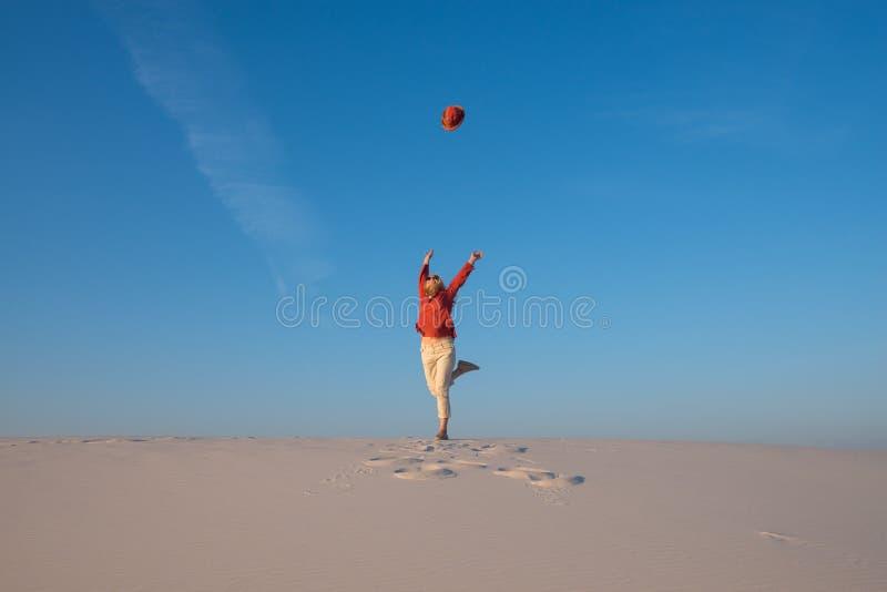 La jeune femme heureuse, blonde saute et jette son chapeau photographie stock