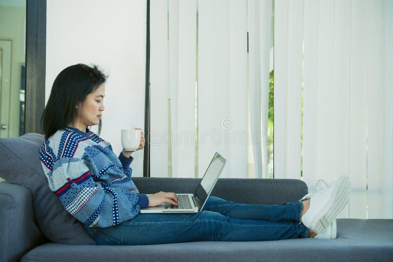 La jeune femme heureuse détend sur le divan confortable et utilise l'ordinateur portable à la maison Photo modifiée la tonalité photos libres de droits
