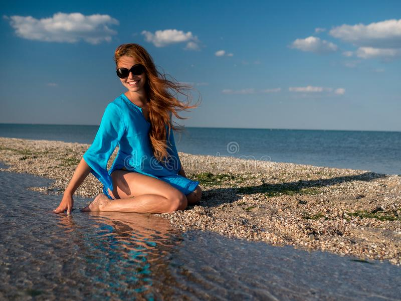 La jeune femme heureuse dans des lunettes de soleil, tunika bleu s'assied au bord de la mer, au rire et aux regards à la mer à la photos libres de droits
