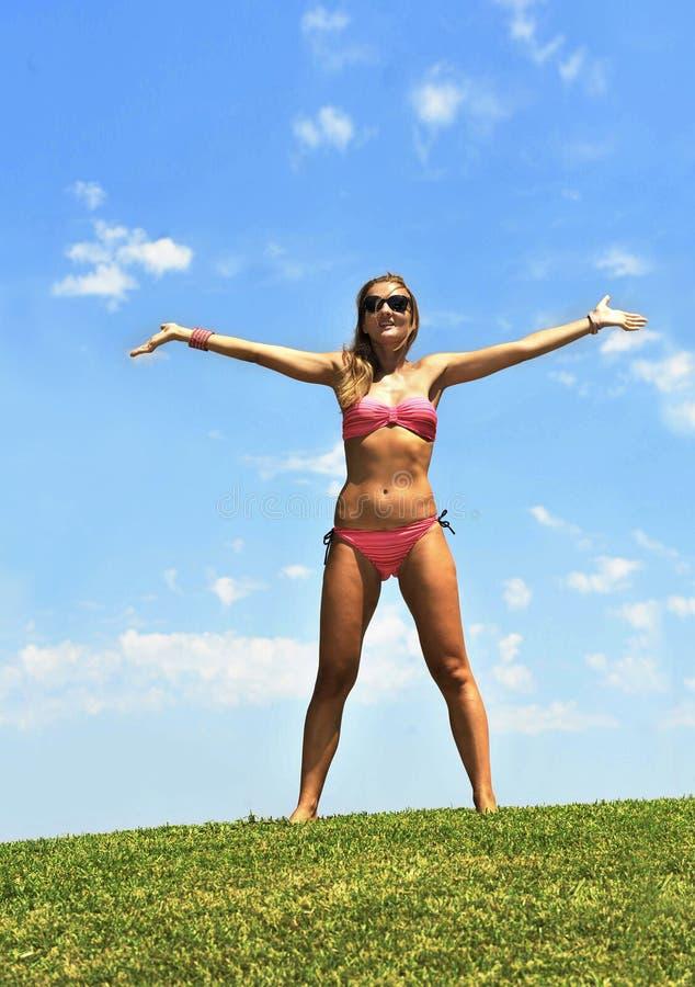 La jeune femme heureuse dans l'ouverture de bikini arme à l'air en ciel d'été image stock