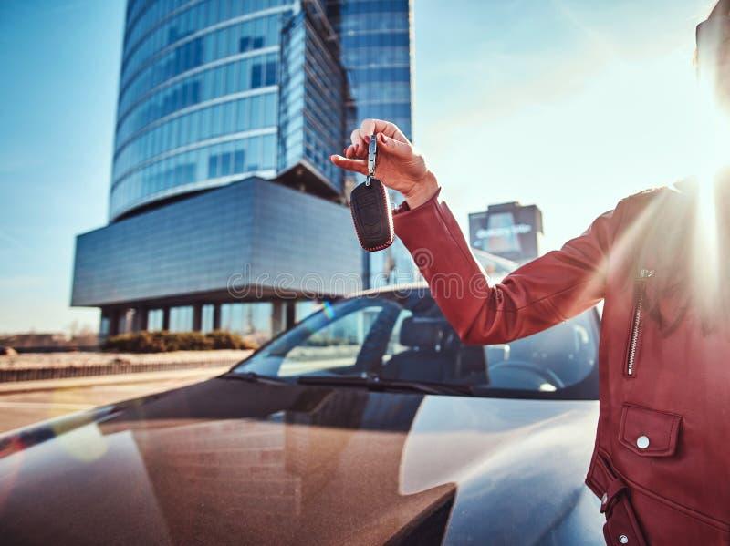 La jeune femme heureuse a juste obtenu des clés de sa nouvelle voiture, qui est behide image stock
