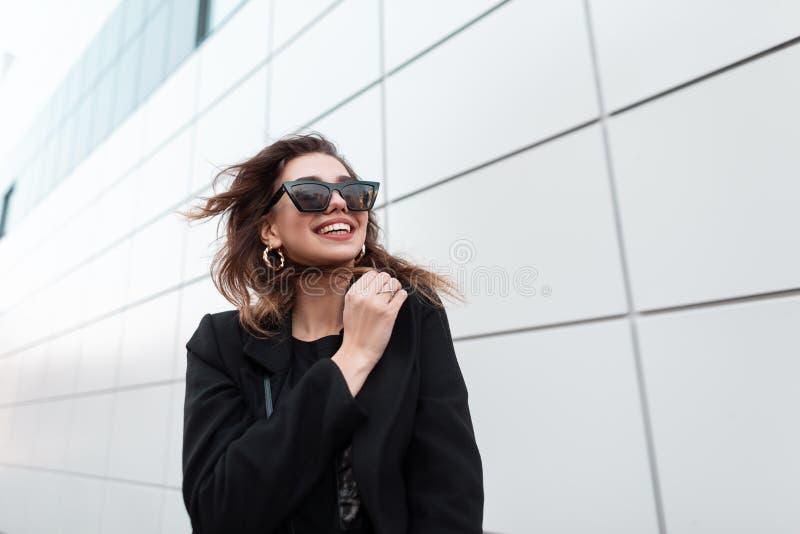 La jeune femme heureuse moderne de hippie dans un manteau élégant noir dans des lunettes de soleil à la mode foncées va et sourit photos libres de droits