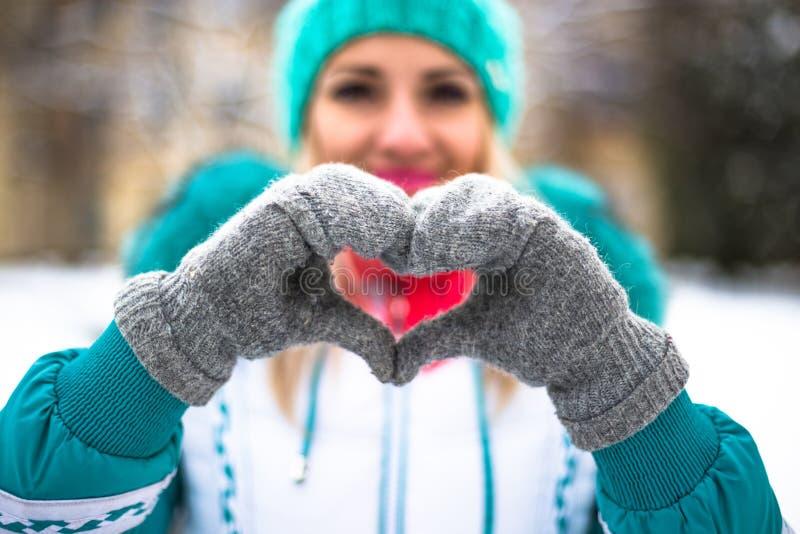 La jeune femme heureuse rendent le coeur avec des mains en parc de ville d'hiver extérieur image libre de droits