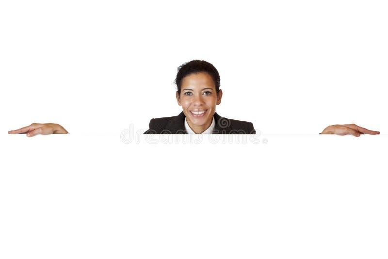 La jeune femme heureuse se penche sur le panneau-réclame blanc photo stock
