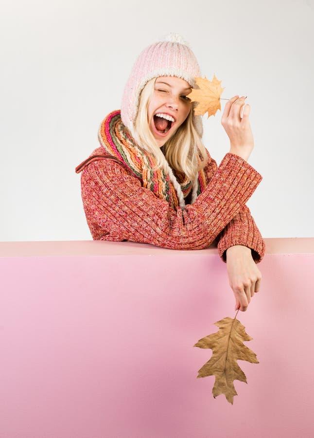 La jeune femme heureuse se préparent au jour de vente d'automne Étonnez la femme jouant avec la feuille et regardant l'appareil-p photo libre de droits