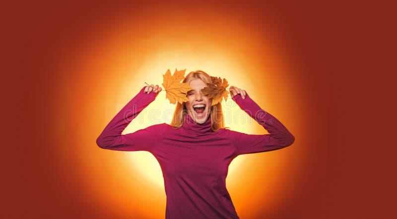 La jeune femme heureuse se préparent au jour ensoleillé d'automne Étonnez la femme jouant avec des feuilles et regardant l'appare image stock