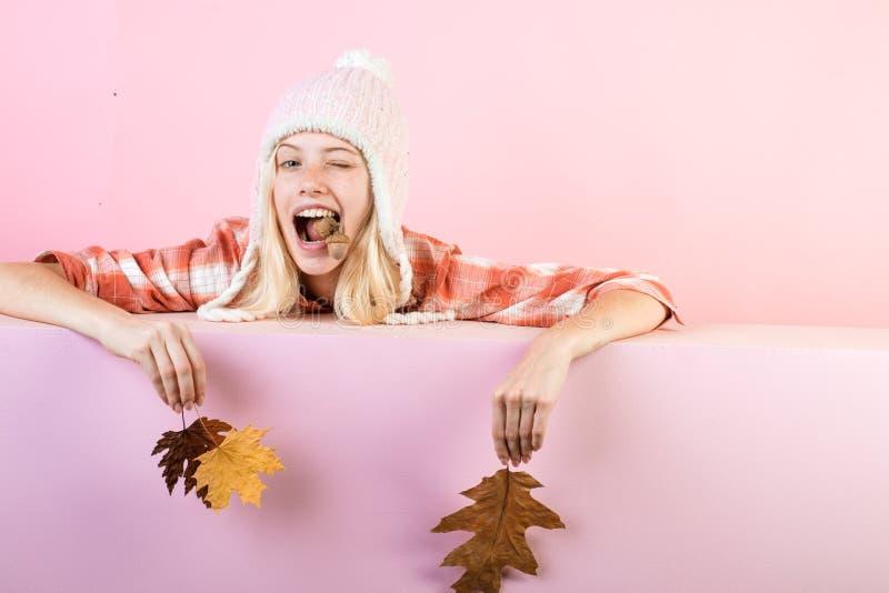 La jeune femme heureuse se préparent au jour ensoleillé d'automne Étonnez la femme jouant avec des feuilles et regardant l'appare photographie stock