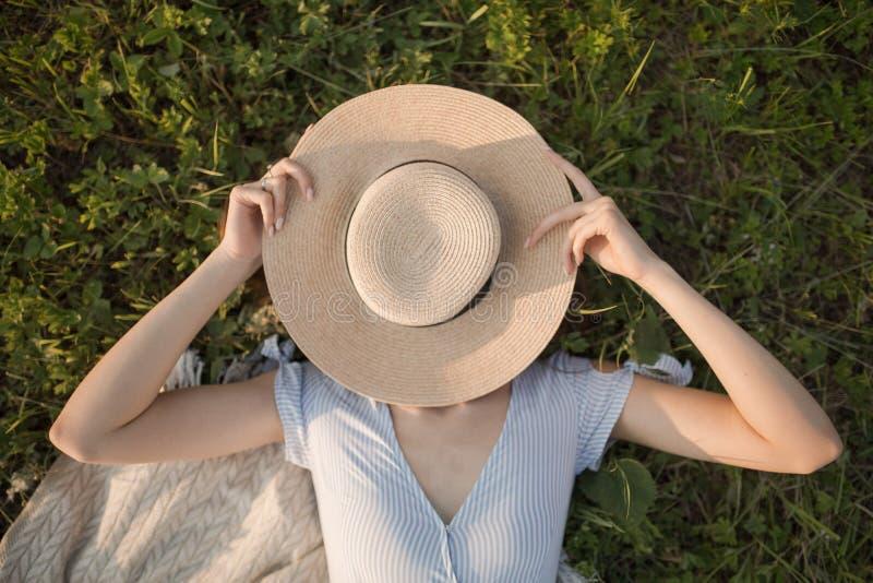 La jeune femme heureuse se situe en parc sur l'herbe verte Vue de portrait d'en haut photo stock