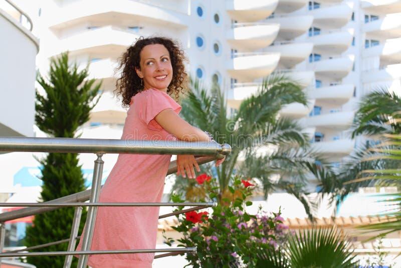 La jeune femme heureuse se tient sur le balcon photo libre de droits