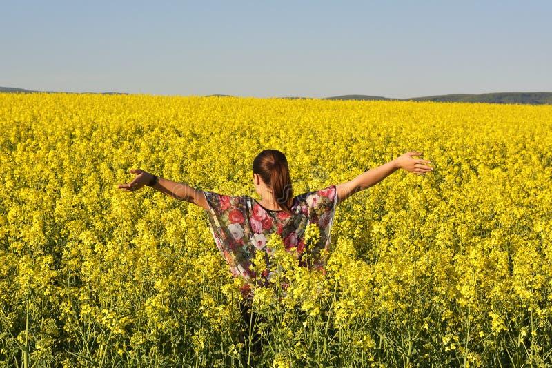 La jeune femme heureuse sur la graine de colza de floraison mettent en place au printemps photographie stock