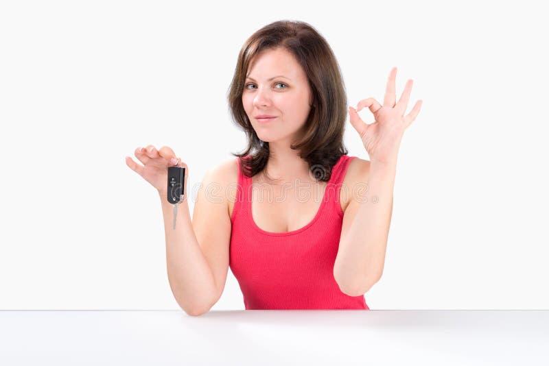 La jeune femme heureuse tient des clés de voiture et montre le geste correct photos libres de droits