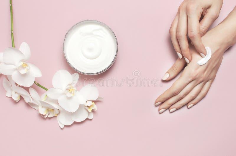 La jeune femme hydrate sa main avec la lotion crème cosmétique a ouvert le conteneur avec l'orchidée blanche comme le lait de Pha images stock