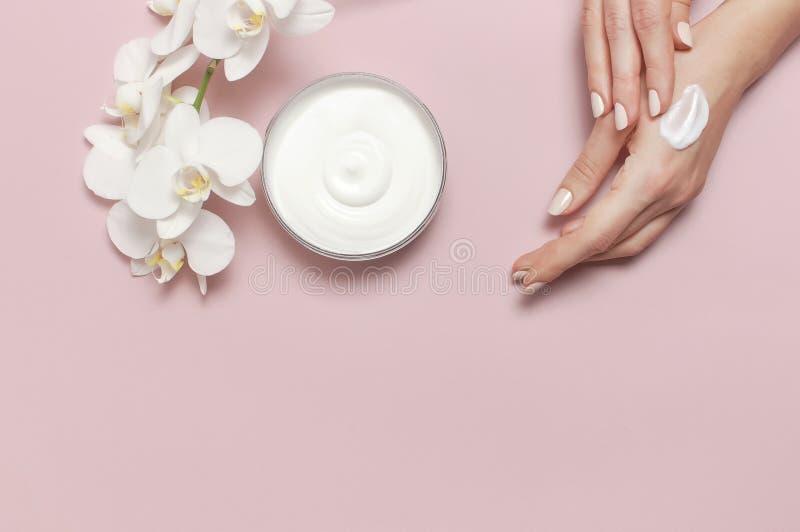 La jeune femme hydrate sa main avec la lotion cr?me cosm?tique a ouvert le conteneur avec l'orchid?e blanche comme le lait de Pha images libres de droits