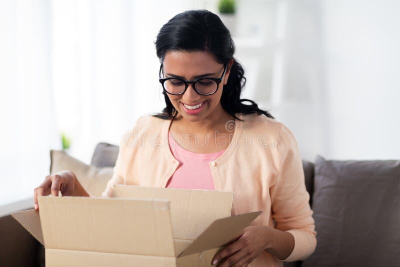 La jeune femme indienne heureuse avec le colis enferment dans une boîte à la maison photos libres de droits