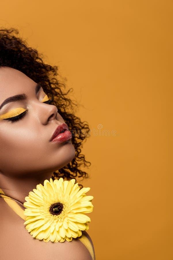 La jeune femme intelligente d'afro-américain avec le maquillage artistique tient la fleur jaune de gerbera image libre de droits