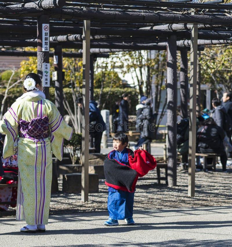 La jeune femme japonaise s'est habillée dans le kimono jaune, avec la petite danse de garçon dans le kimono bleu, Asakusa, Japon, image stock