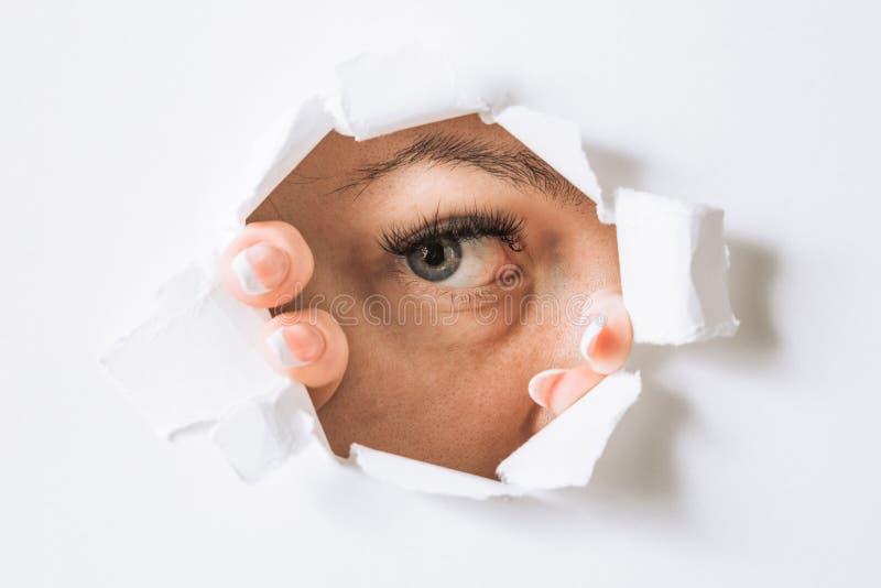 La jeune femme jette un coup d'oeil par un trou dans un mur blanc de papier image libre de droits