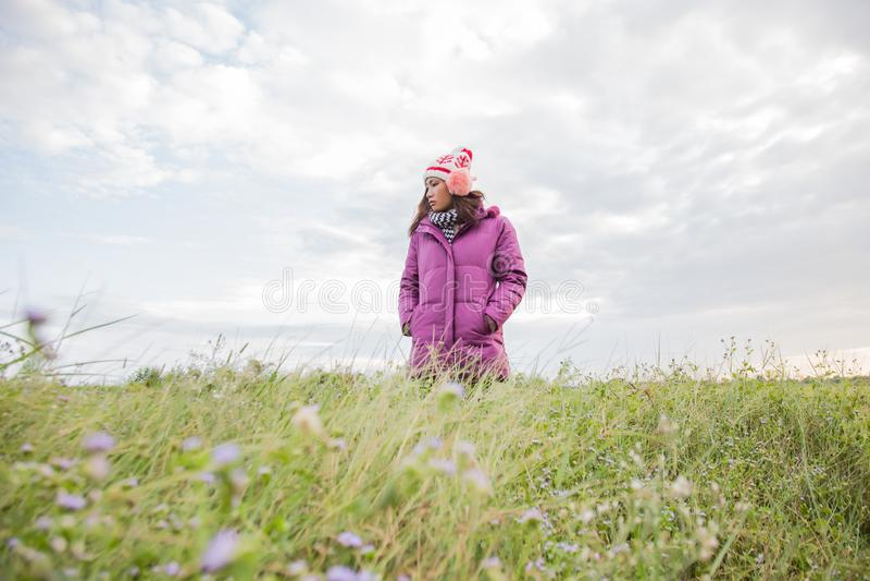 La jeune femme jouait dans un domaine des fleurs ? l'air d'hiver photographie stock