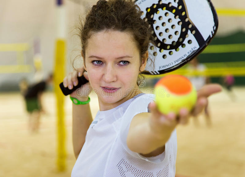 La jeune femme joue au tennis de plage sur la cour couverte image libre de droits