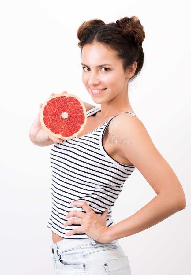 La jeune femme joyeuse démontre un pamplemousse Foof sain et naturel photo stock