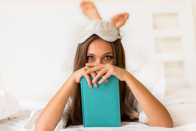 La jeune femme a lu le livre dans le lit photographie stock libre de droits