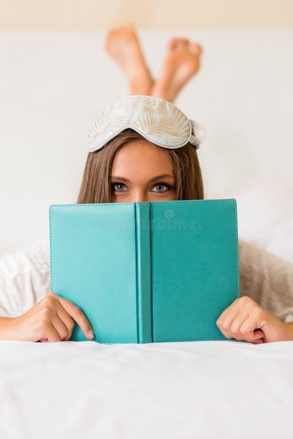 La jeune femme a lu le livre dans le lit images libres de droits