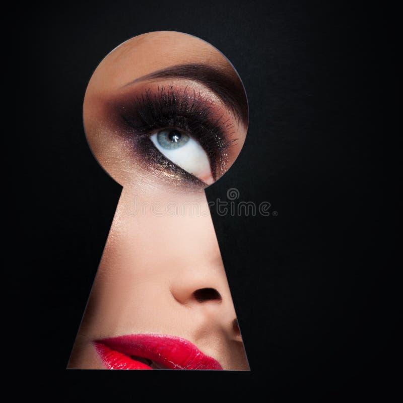 la jeune femme luxueuse regarde quelque chose secrète dans le trou de la serrure Le concept du secret de la beauté, nouveaux cosm image stock